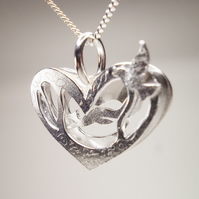 pendant A silver pine marten runs through a nighttime scene pendant