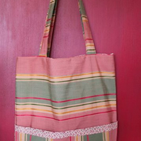 Tote bag with pockets on outside & inside, cream & red contrast lining & border.