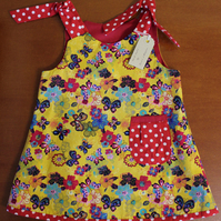Butterfly Print Dress with Red & White spot pocket detail. 2 Years.