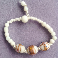 White patterned glass beaded stretchy bracelet.