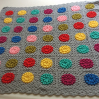 Handmade crochet blanket, grey background with multicolour circles