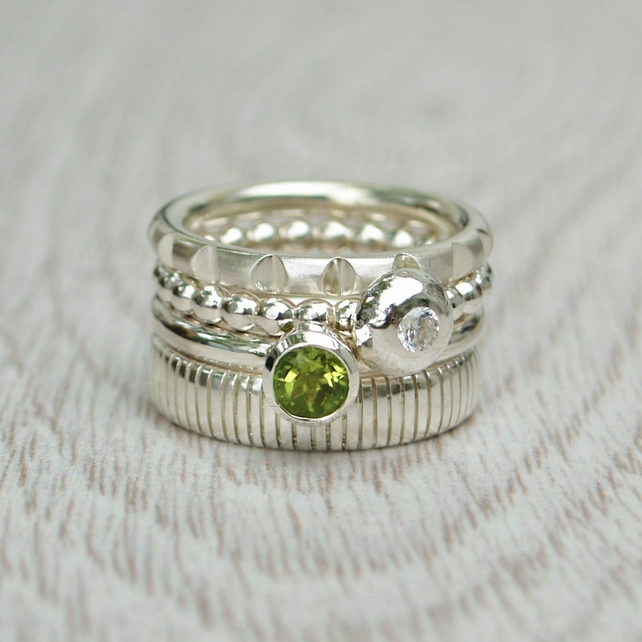 A set of four silver stacking rings - Notched - CZ ball - Peridot - Stripes