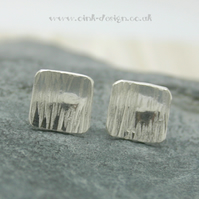 Sterling silver square stud earrings with a hammered finish and slightly domed