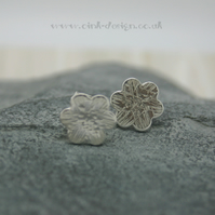 Sterling silver flower stud earrings with a textured finish