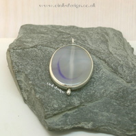 A clear piece of agate with mauve set in sterling silver spectacle setting