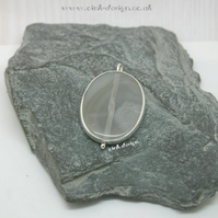 A slice of clear and white agate set in sterling silver spectacle setting