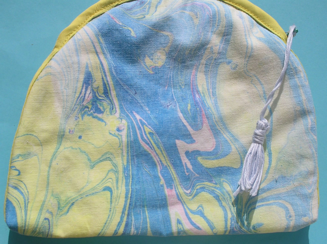 A zipped bag in Unique hand marbled fabric