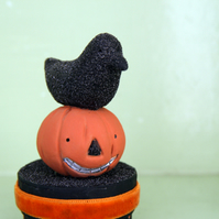 Primitive folk art Halloween crow figure on a pumpkin