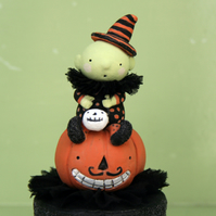 Primitive folk art Halloween baby witch on a pumpkin
