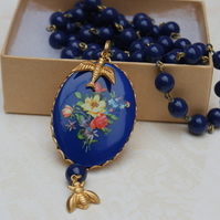 Pretty Blue Floral Cabochon on glass bead chain....