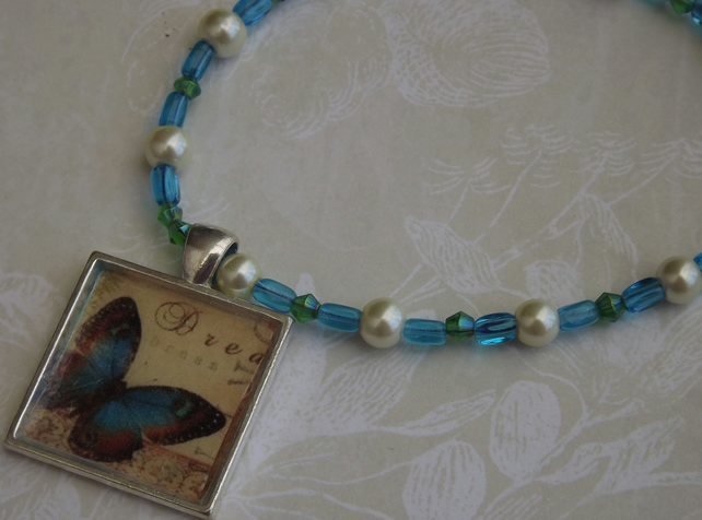 Blue Butterfly, silver pendant on beaded necklace with faux pearls.