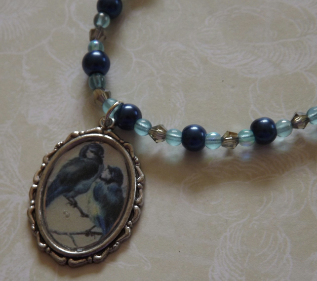 Blue Birds, silver pendant on a beaded necklace