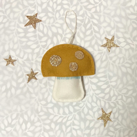Mustard yellow handstitched felt toadstool with gold sparkly spots