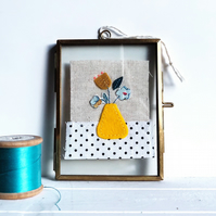 Yellow flower vase fabric collage in a glass and metal frame