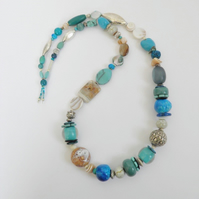 Long, sea-shore coloured, statement necklace.
