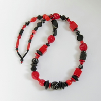 Long, chunky, red and black necklace.