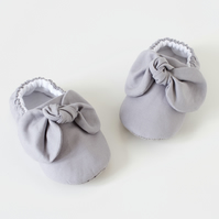 light grey cotton baby girls shoes with knotted bow detail on front.