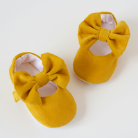 Mustard corduroy baby girls shoes with large bow on strap.