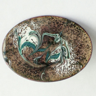 enamel brooch - oval: scrolled white and dark green on black over clear