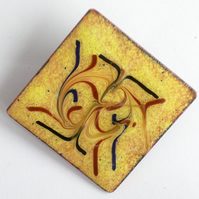 square brooch - scrolled red brown and black on gold over clear enamel