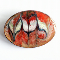 large oval brooch - scrolled white and dark blue over red on clear enamel