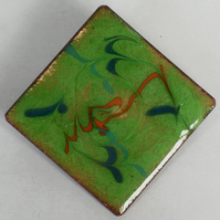 brooch - scrolled red and blue on green over clear enamel