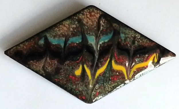 diamond shape - scrolled turquoise, black, yellow over red on clear enamel