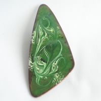 brooch: triangular - scrolled white and black on green over clear enamel