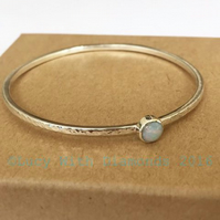 Hammered finish sterling silver bangle with round opal