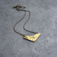 Delicately textured gold plated mini geo pendant on white enamelled chain