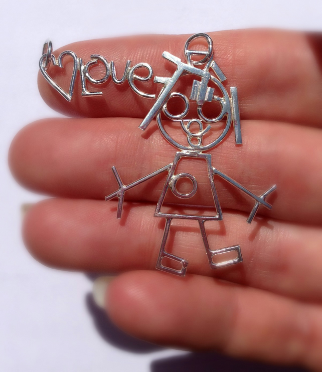 The girl with the rubber band hair. A silver pendant from a childs drawing.