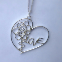 A sterling silver pendant designed from two childrens drawings