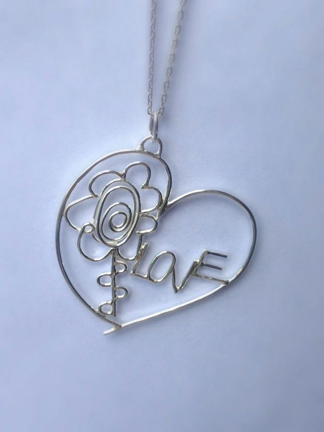 A personalised bespoke sterling silver pendant from two childrens drawings