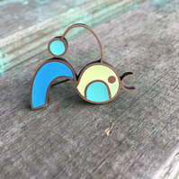 A cheerful bird brooch with resin colour handmade using traditional techniques