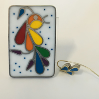 A Rainbow bird pendant and brooch in brass and resin.