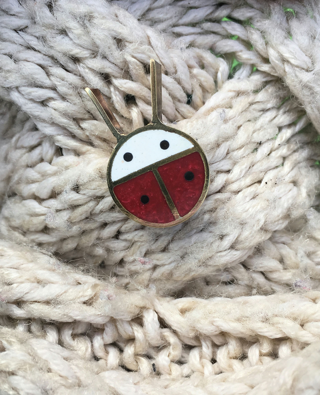 A tiny ladybird pin brooch in resin and metal.