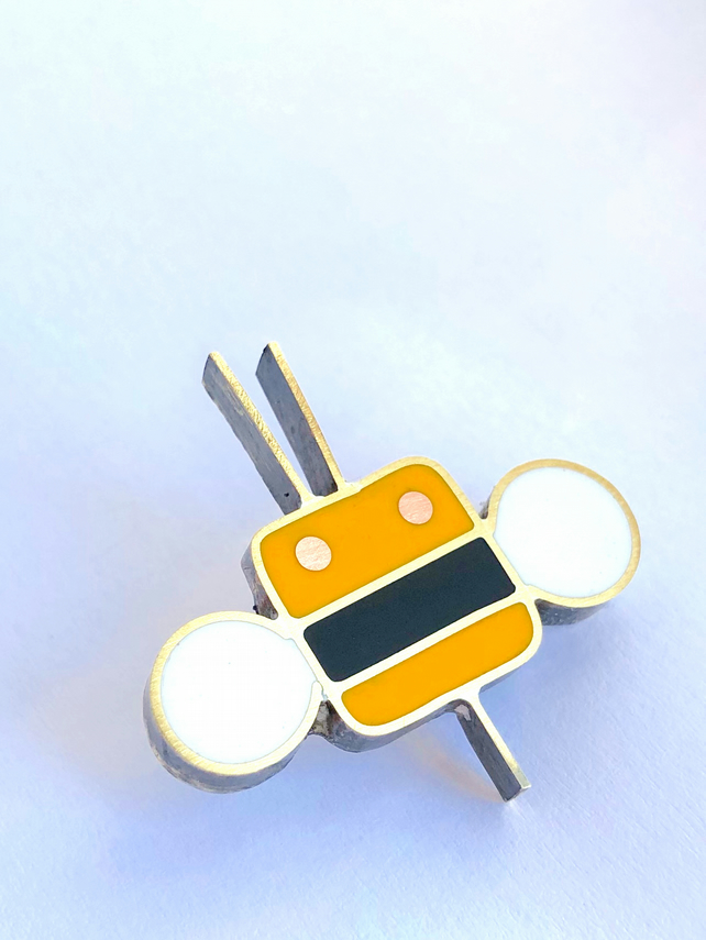 A tiny bee pin brooch in resin and metal