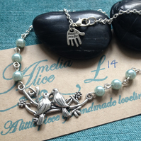 Tibetan silver lovebirds necklace with blue glass pearl bead detail.