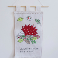 Fabric wall hanging with sleeping hedgehog design