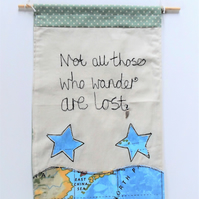 Fabric wall hanging with travel theme applique