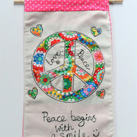 Fabric wall hanging with hippy peace sign applique