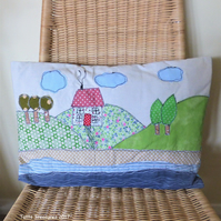 Cushion with a house by the sea applique