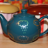 Hand drawn teal porcelain teapot with metallic rain clouds weather design