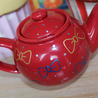Hand drawn small red porcelain teapot with metallic bows and polka dots pattern