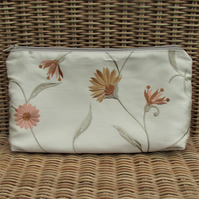 Cosmetic bag in embroidered gold fabric with floral pattern