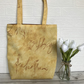 Golden yellow tote bag with unusual handwriting pattern in red
