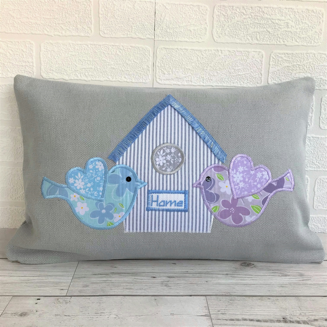 Grey rectangular cushion with blue and lilac floral birds and striped birdhouse
