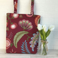 Burgundy tote bag with stylised floral seed head, fruit and foliage print