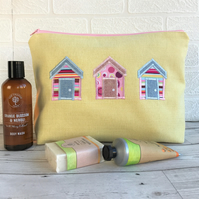 Beach huts toiletry bag, wash bag in yellow fabric with three bright beach huts
