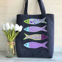 Fish tote bag in dark blue with four colourful fish in purple, blue and green